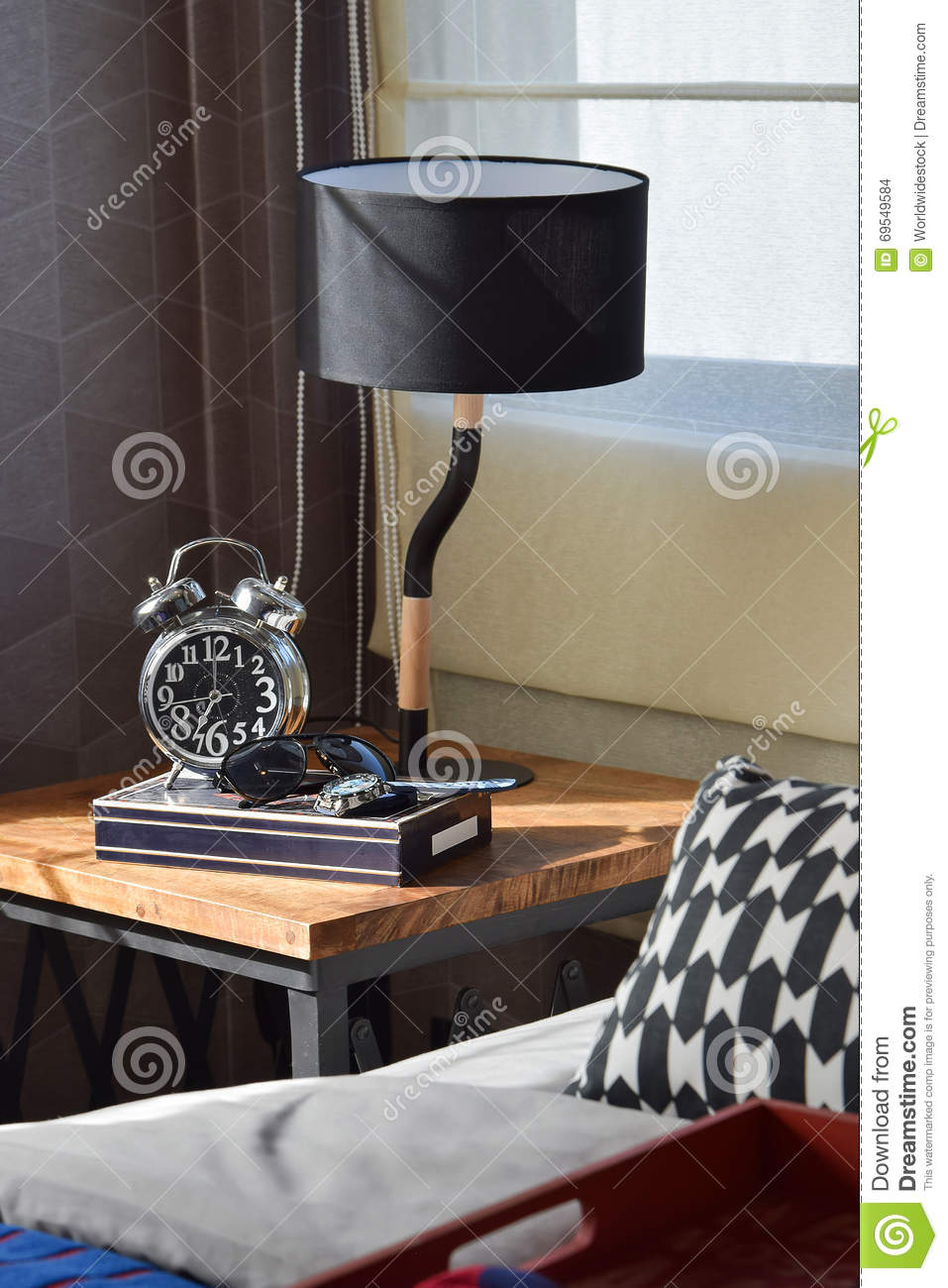 Modern Bedroom With Black Lamp And Alarm Clock On Wooden Table At Home