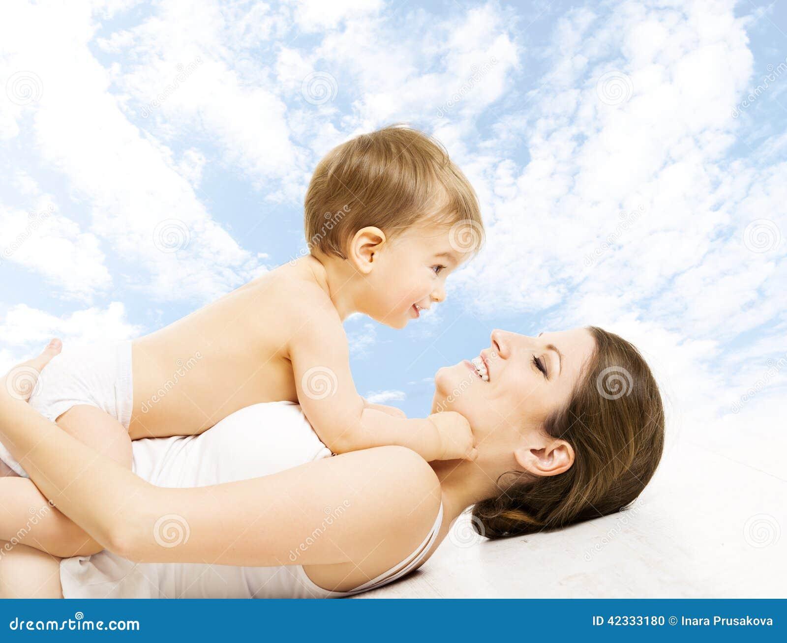 Modern behandla som ett barn lyckligt spela Barn i blöjan som omfamnar mamma över s