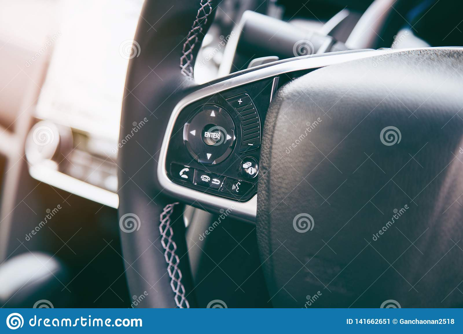 Modern black steering wheel with multifunction buttons for quick control, close-up in the car
