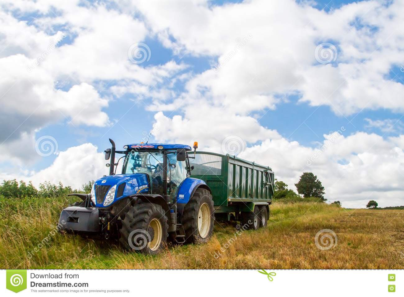 Tractor Pulling Trailer : Green tractor and blue sky editorial photo