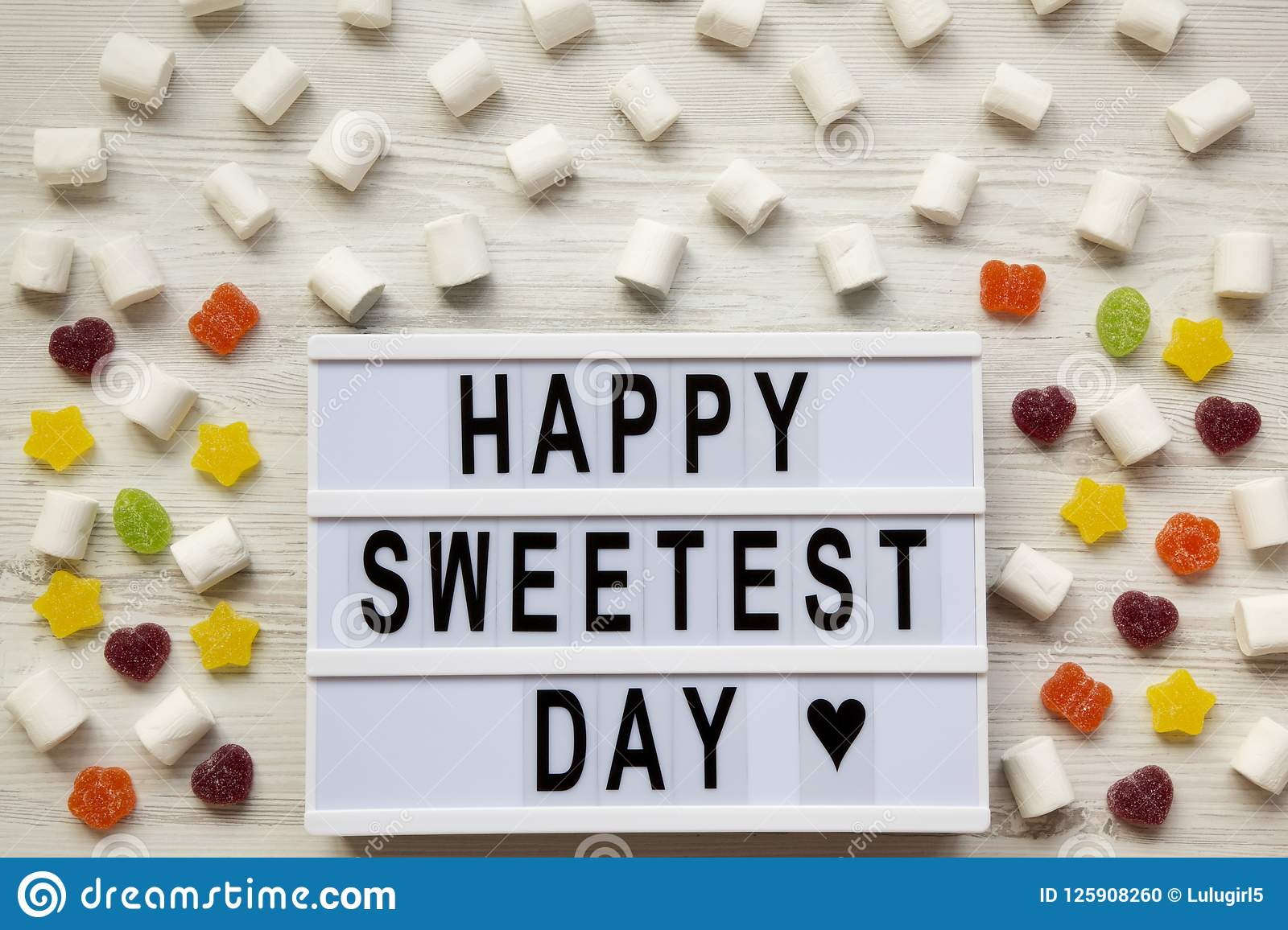 Modern board with text `Happy Sweetest Day` word and candy over white wooden surface, top view. From above, flat lay
