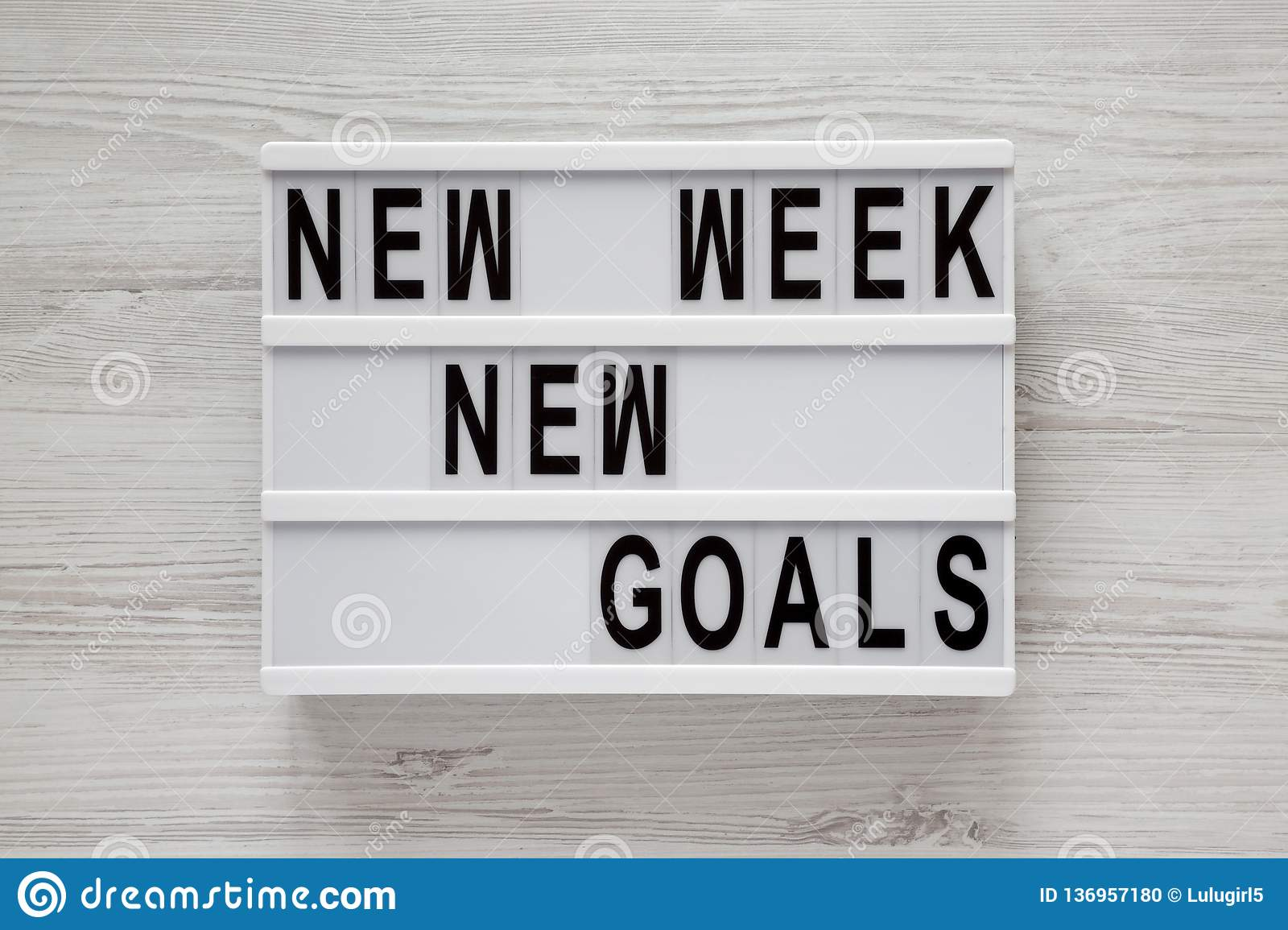 Modern board with text `New week new goals` over white wooden surface, top view. From above, flat lay, overhead