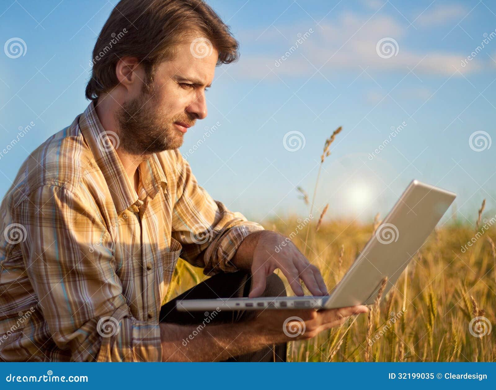 Modern bonde på vetefält med bärbara datorn