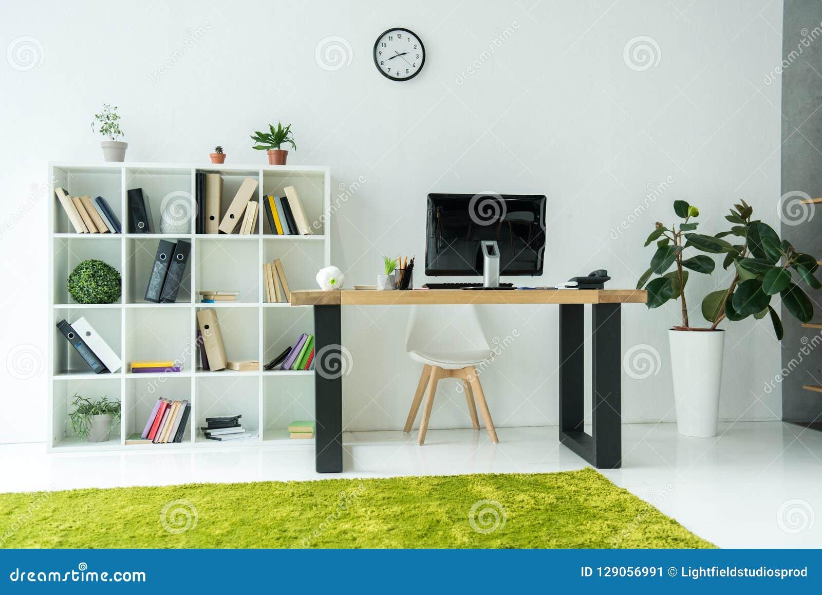Modern bureaubinnenland met computermonitor op lijst en boeken met omslagen
