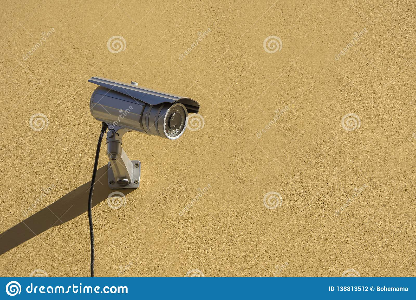 Modern CCTV camera on yellow building wall
