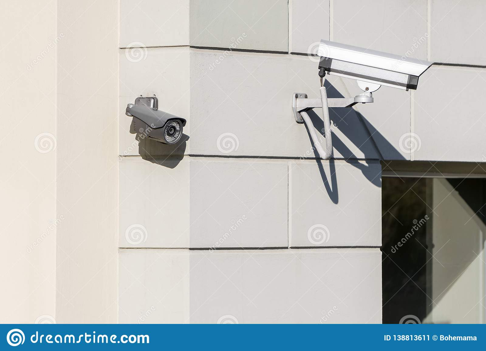 CCTV cameras on modern white building wall in city