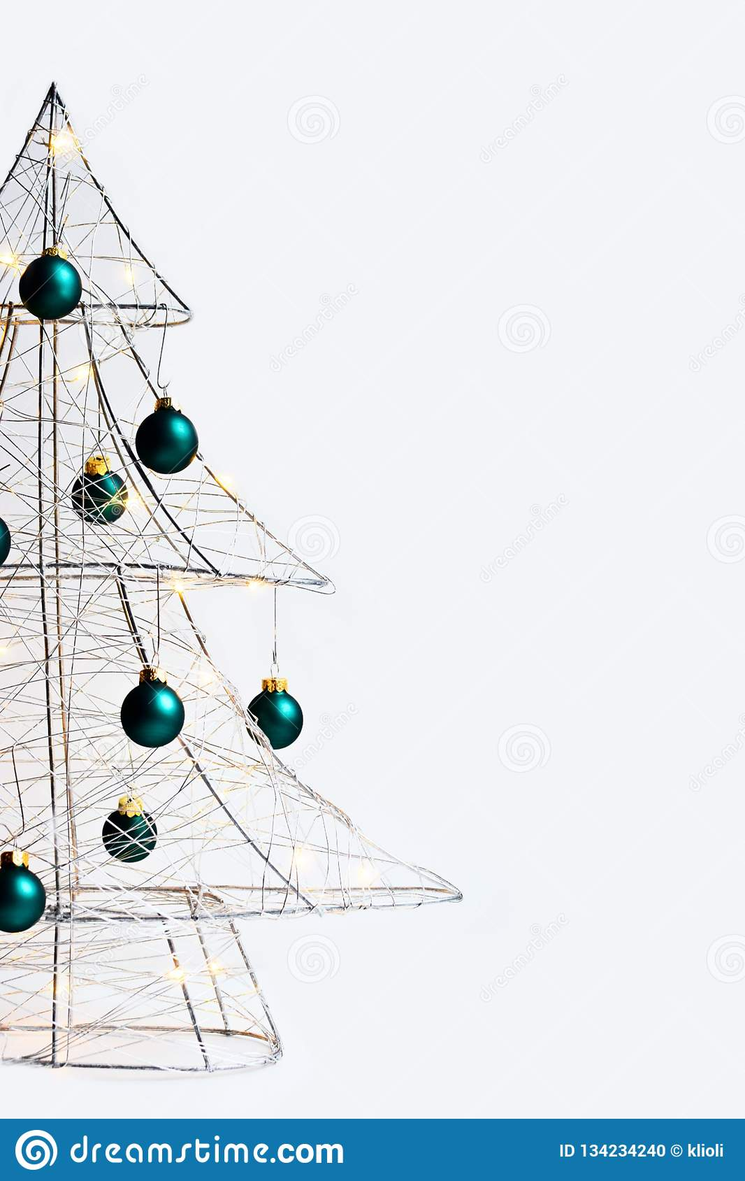 Modern Christmas tree made of silver metal wire, wrapped in a glowing garland and decorated with green balls