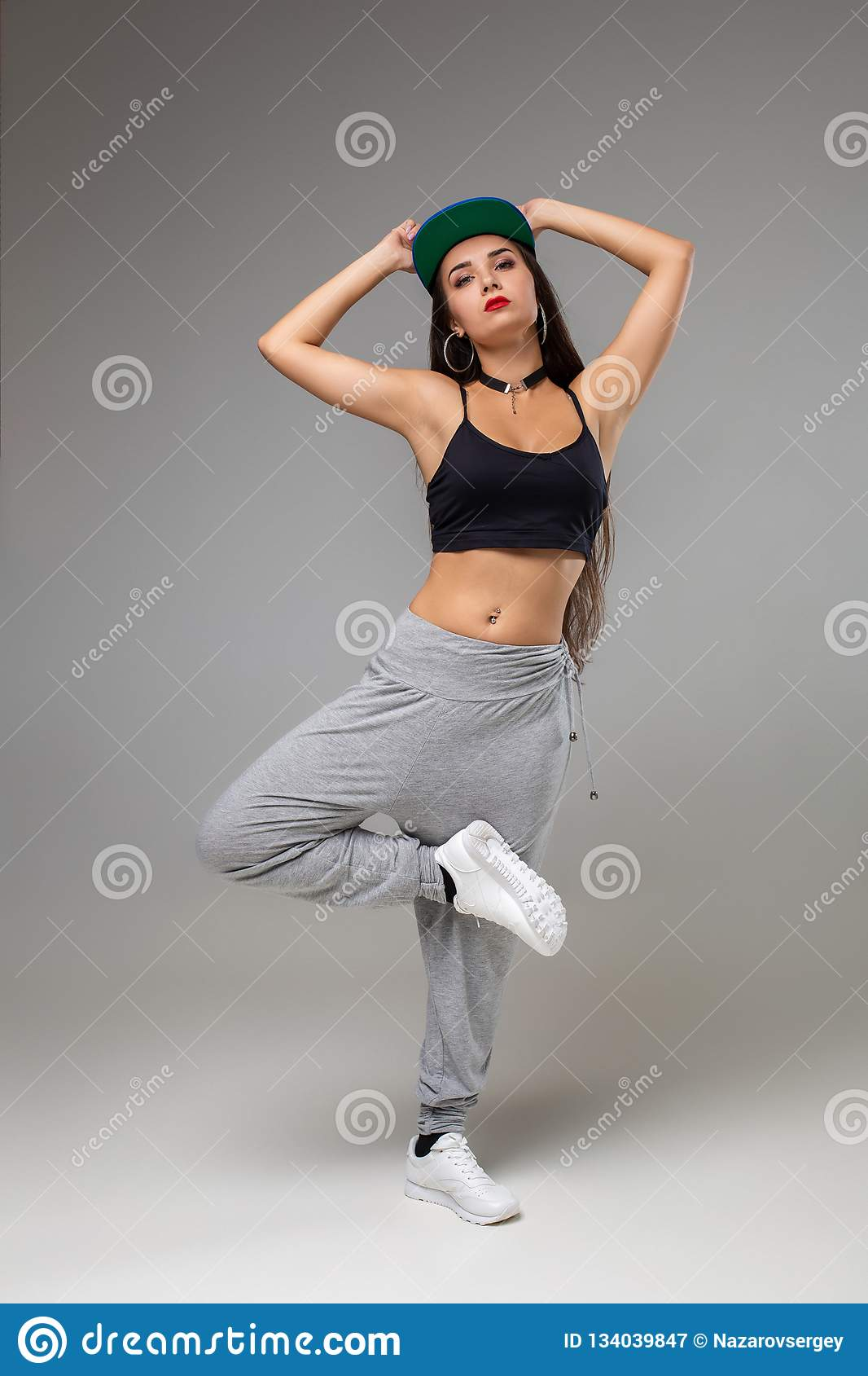 Modern Dancer Poses In Front Of The Gray Studio Background