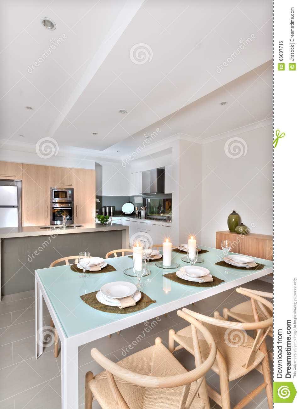Modern Dining Room Setup With Candles Flashing In Front Of The Kitchen
