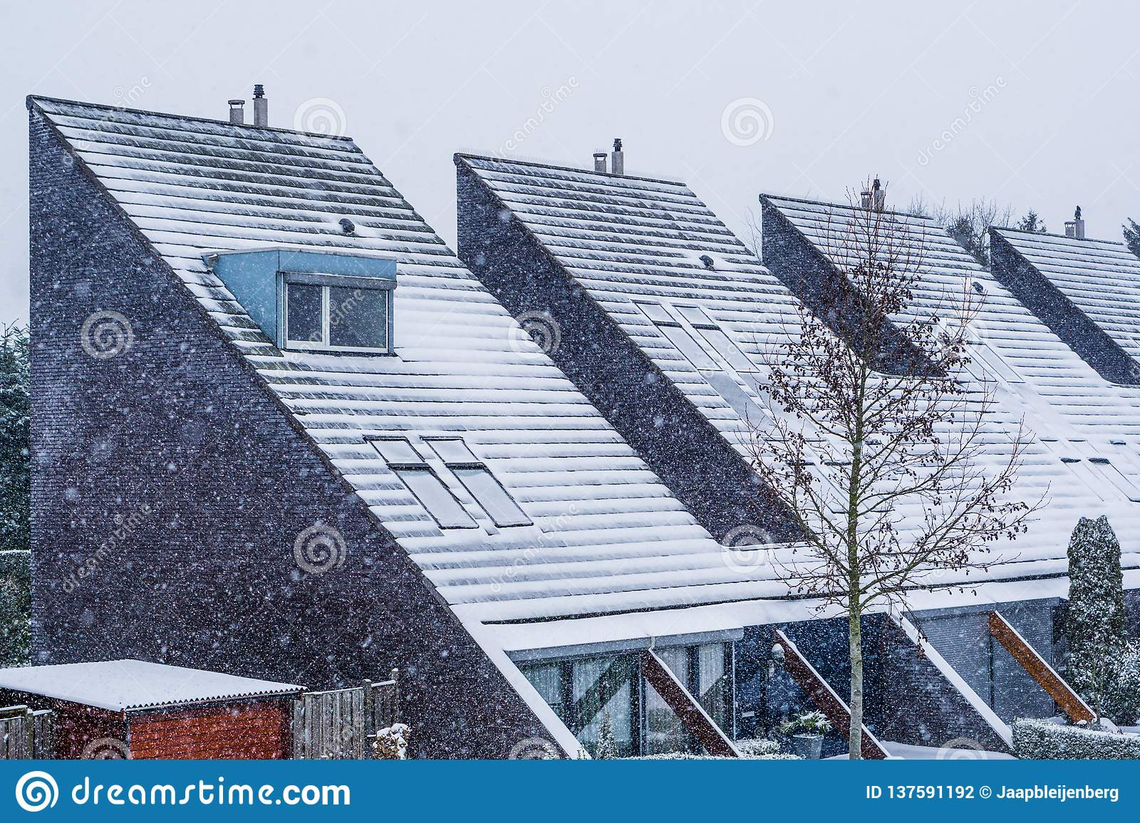 Modern dutch pointy rooftops covered in snow, Modern neighborhood during winter season, snowy cold weather in the Netherlands