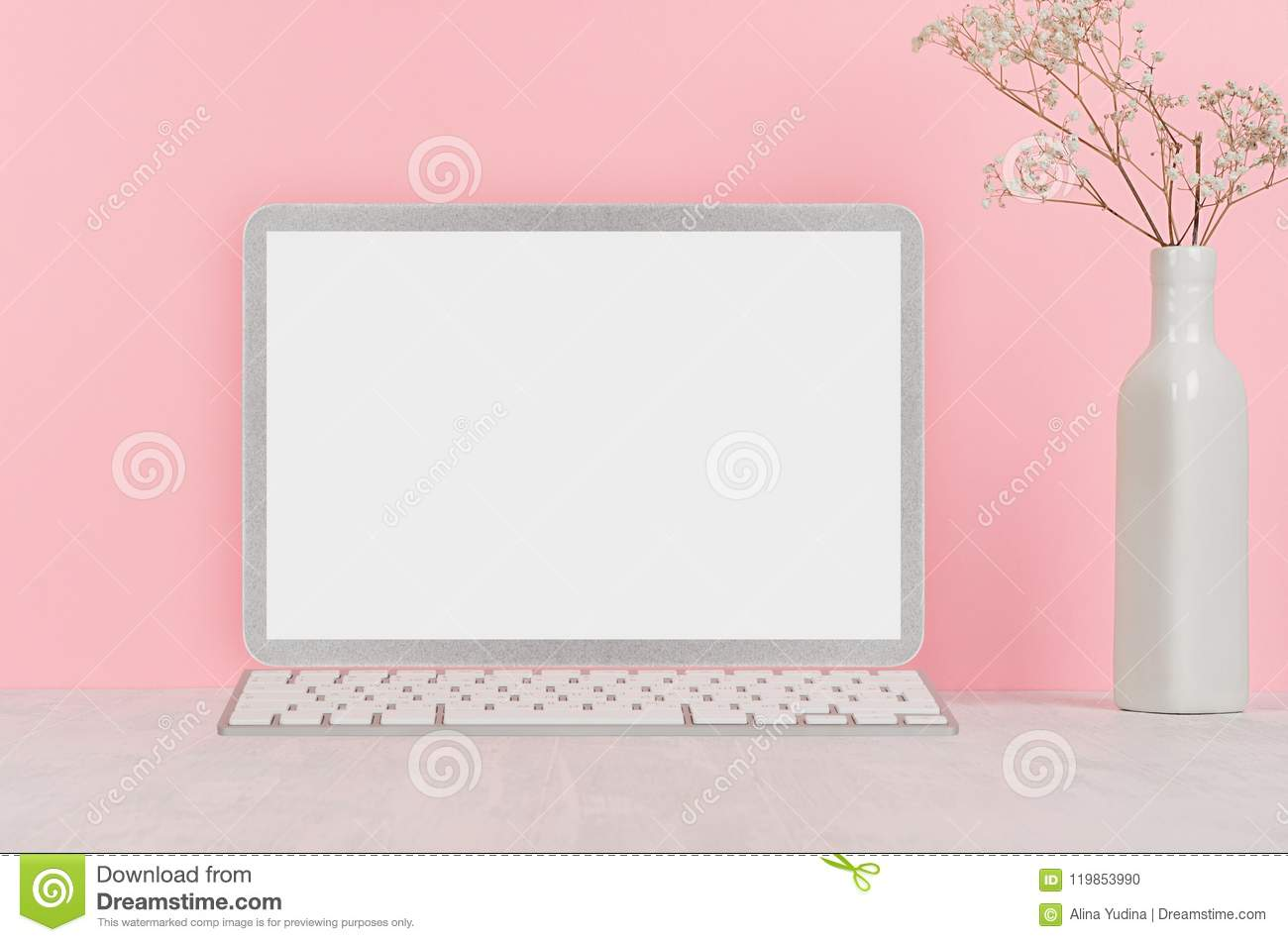 Modern fashion workplace - silver laptop with blank screen, white stationery on soft pink background.