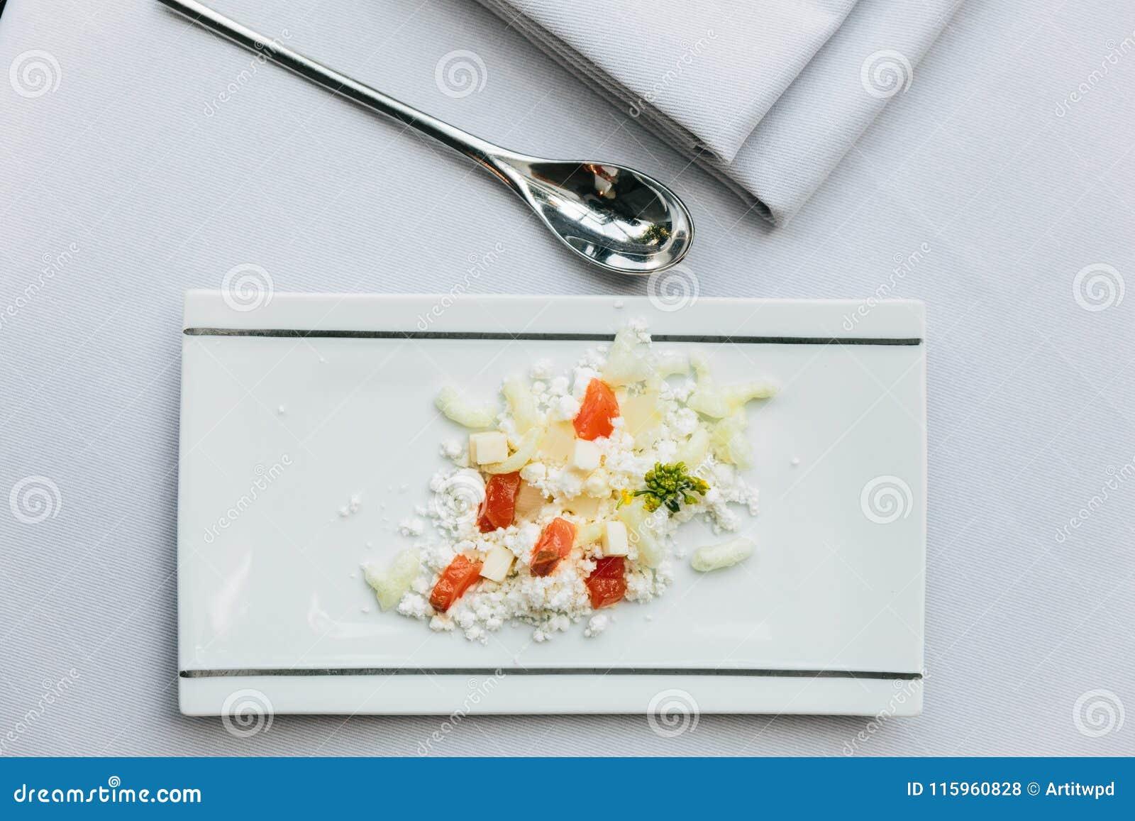 Modern Frans voorgerecht: verbrijzeling en besnoeiingskaas met gedobbelde tomaat diende op witte rechthoekplaat met zilveren lepe