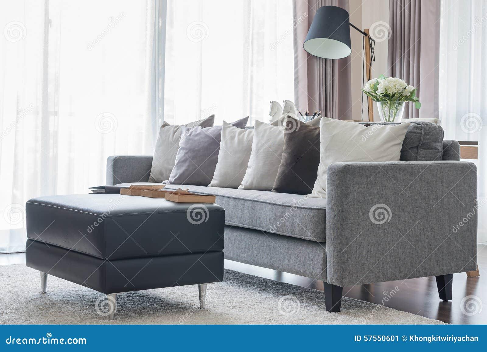 Modern grå soffa med kuddar och den svarta tabellen i vardagsrum ...