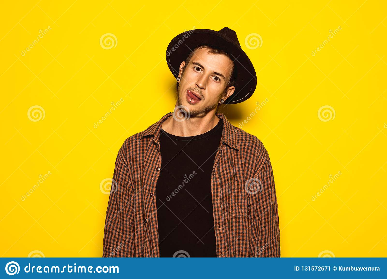 a96c6213bf8 Modern and handsome Guy with a black hat on a yellow background. Young man  cool dress