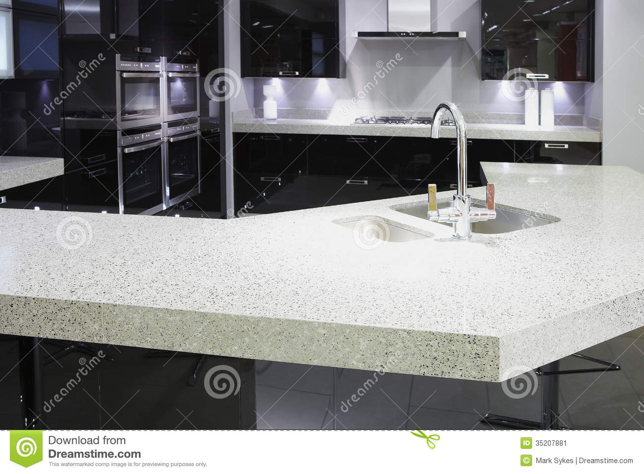 ... high end luxury kitchen with black doors and white marble work tops