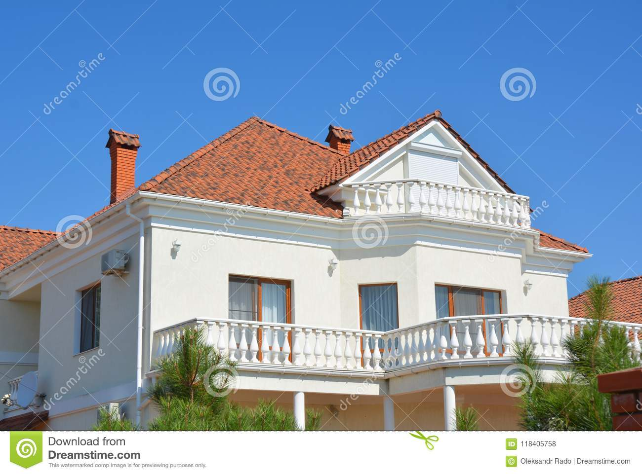 Luxury modern home with attic balcony and clay tiles roof.