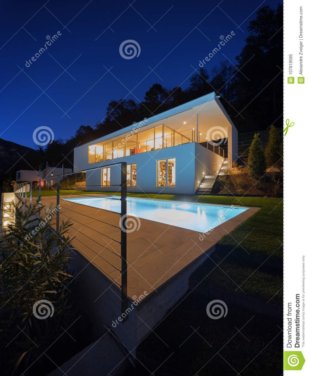 Modern house exterior in the night lights on