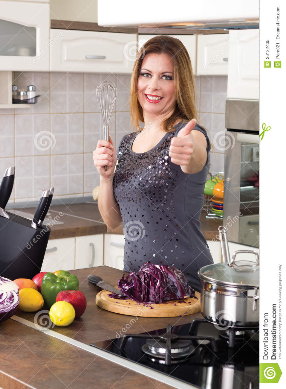 Modern housewife prepare a meal and shows a thumbs up for Modern housewife