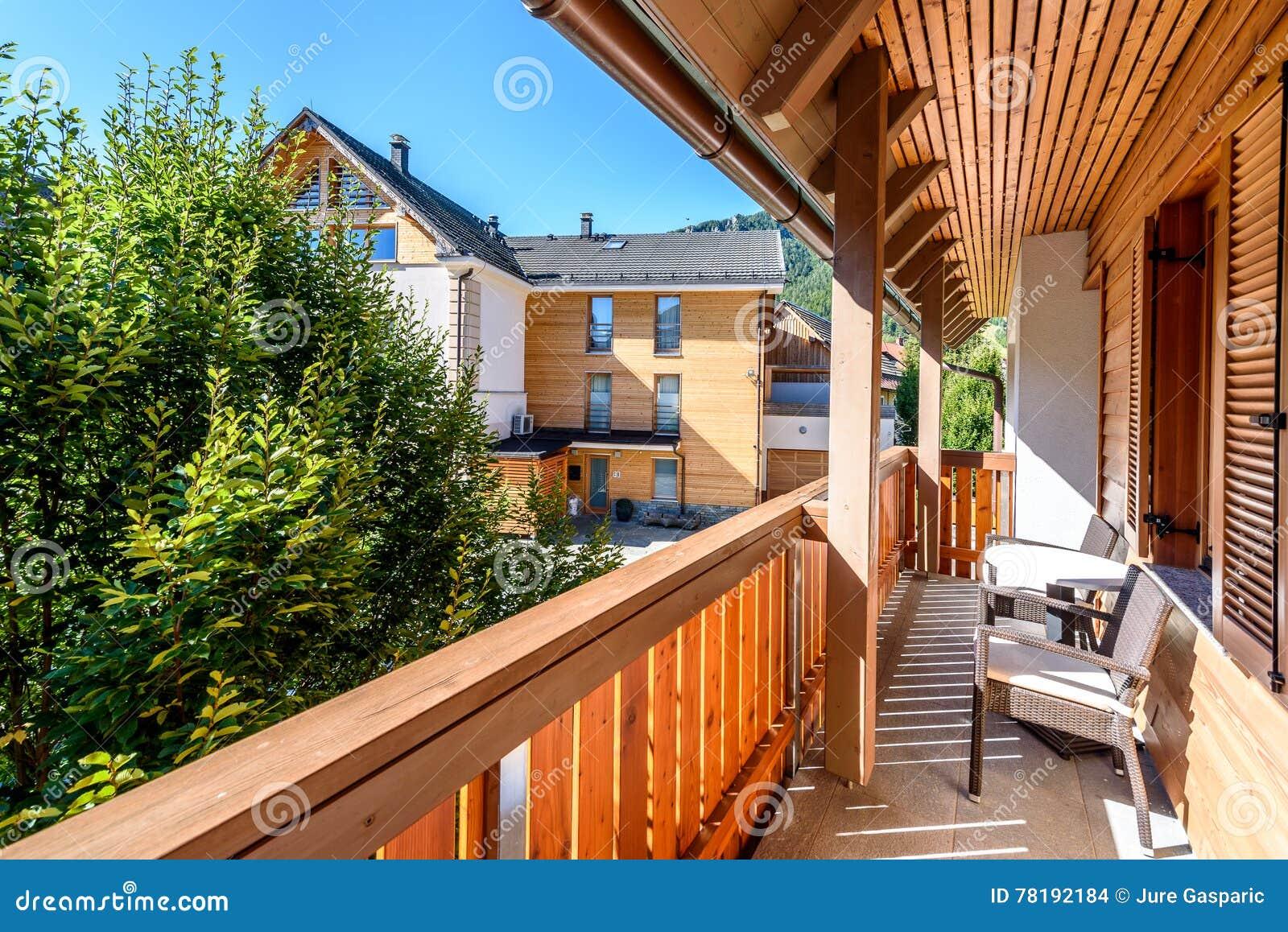 Modern houten terras balkon met lijst en stoelen stock foto