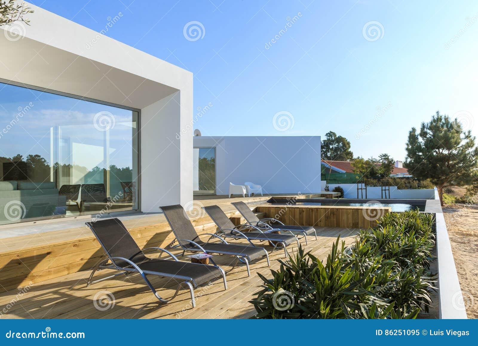 Modern huis met tuin zwembad en houten dek stock afbeelding