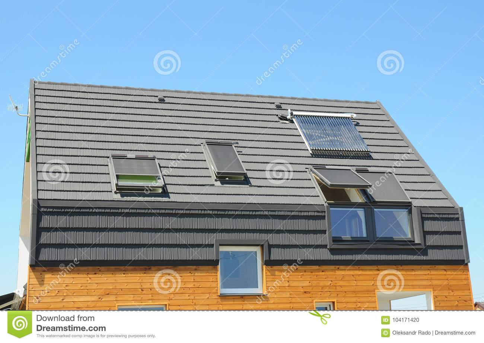 Modern huisdak met zonnewaterverwarmer zonnepanelen en dakramen
