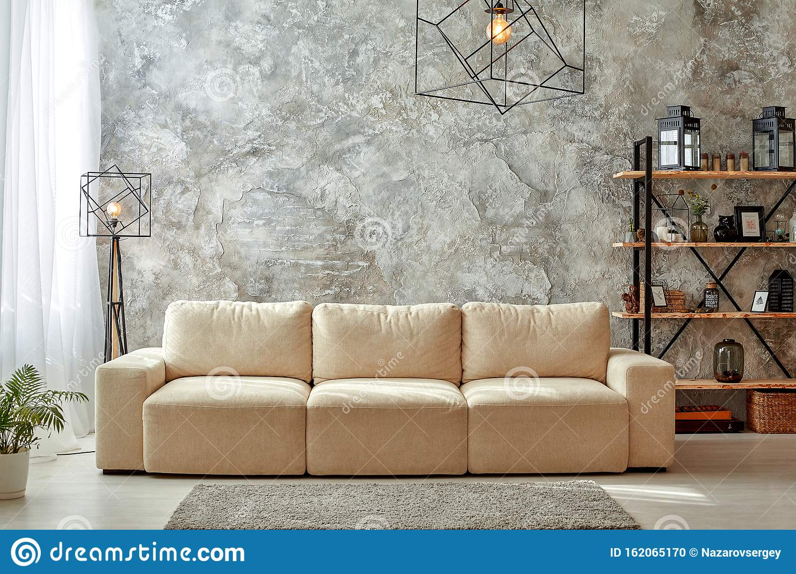Modern Interior Of Living Room With Gray Walls Beige Sofa Floor Lamp And Chandelier Light Carpet Shelf With Frames Stock Photo Image Of Loft Laminate 162065170