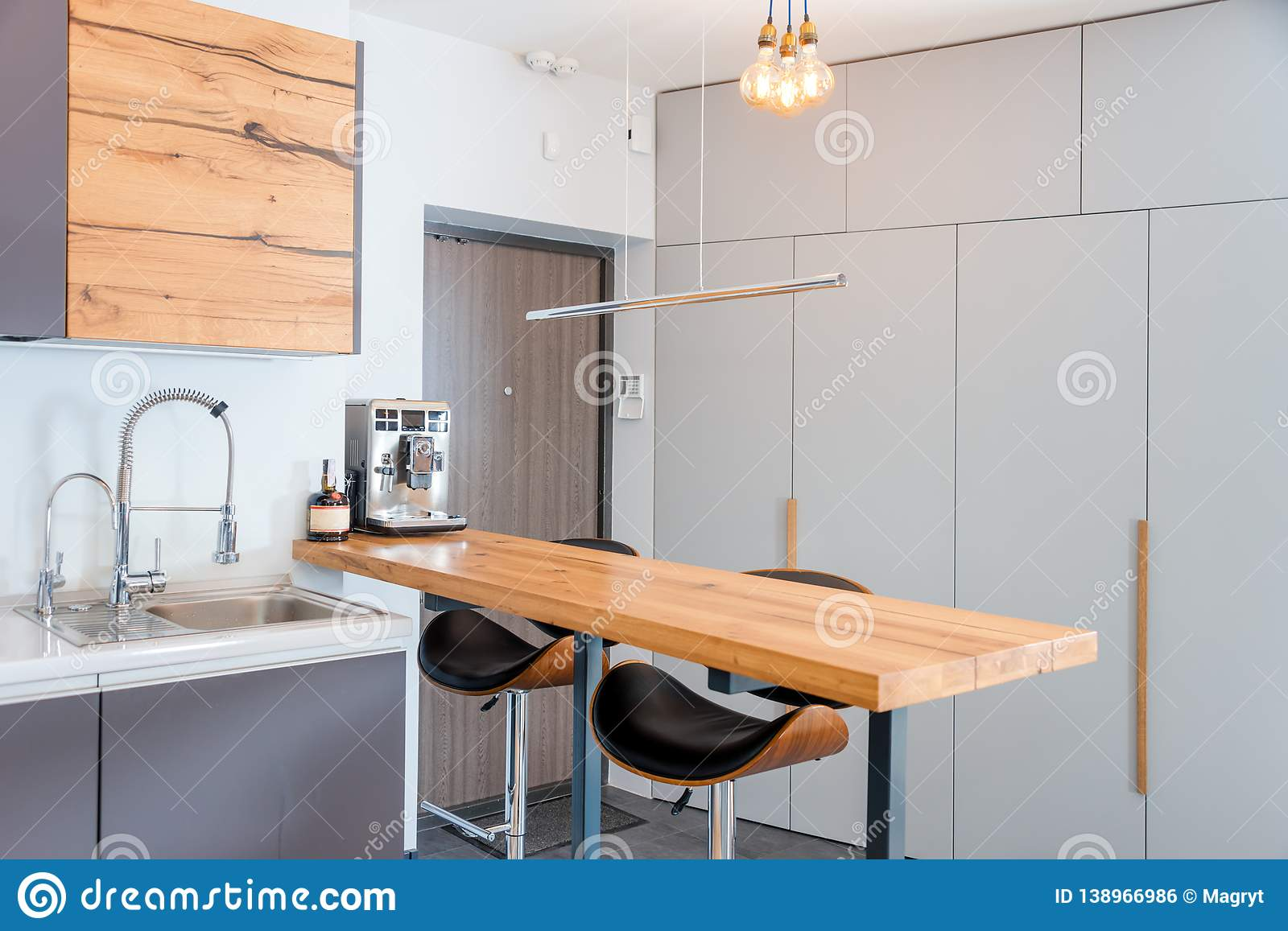 Modern Kitchen Interior With Lights On Brown Wooden Table And Bar Stools Coffee Machine Contemporary Interior With Stock Photo Image Of Apartment Luxury 138966986