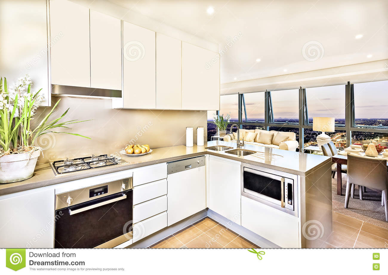 Modern kitchen interior with living room area at evening.