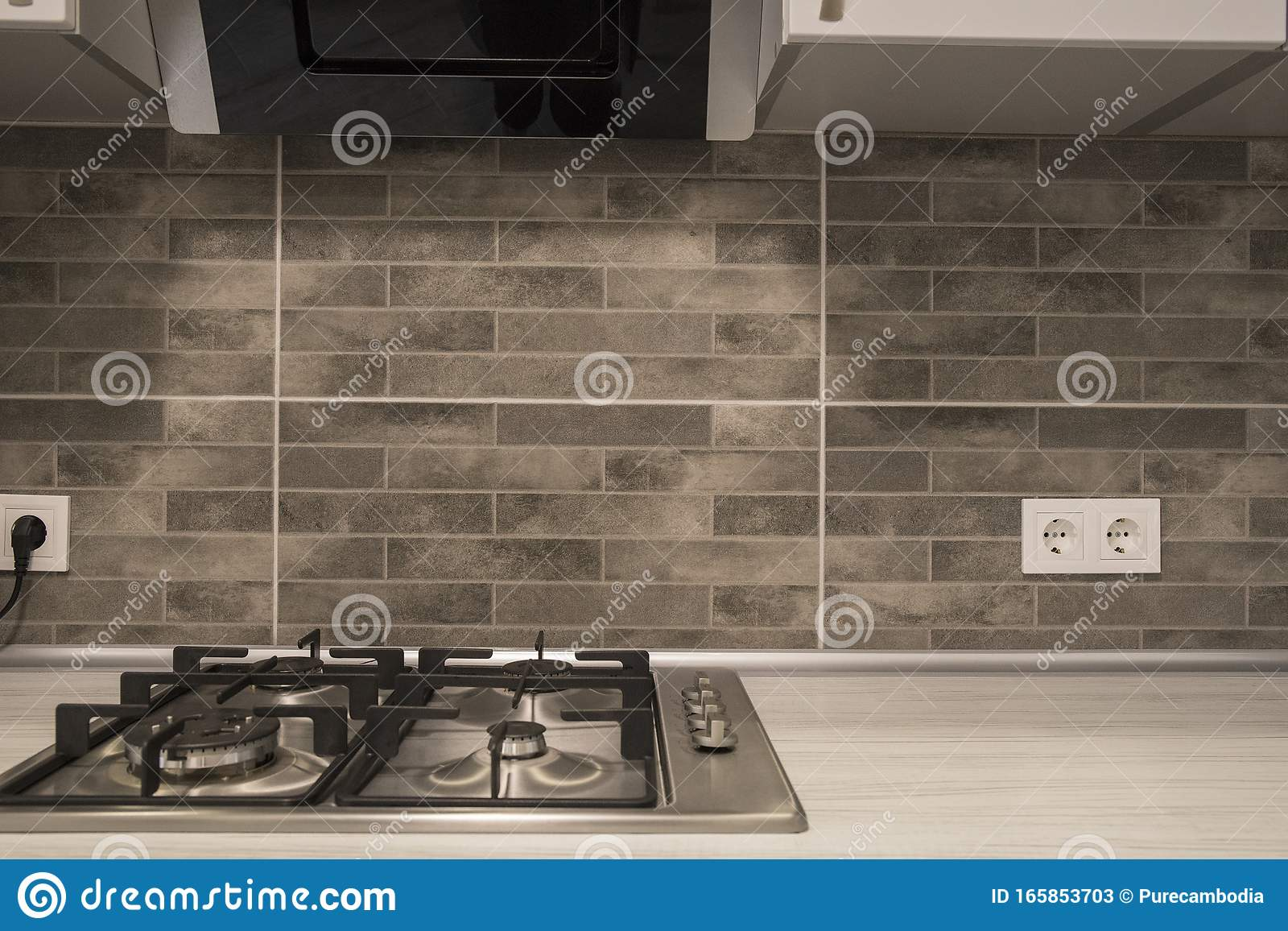 - Modern Kitchen Interior With Stainless Steel Gas Cook-top And Grey