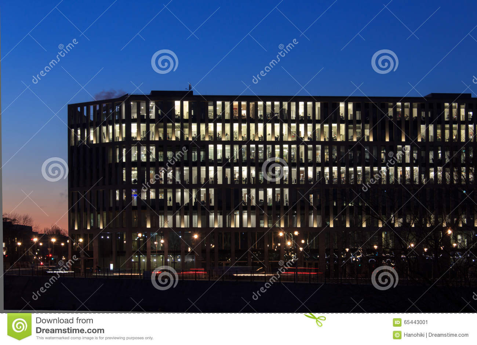 Modern kontorsbyggnadfasad, folk som arbetar på natten