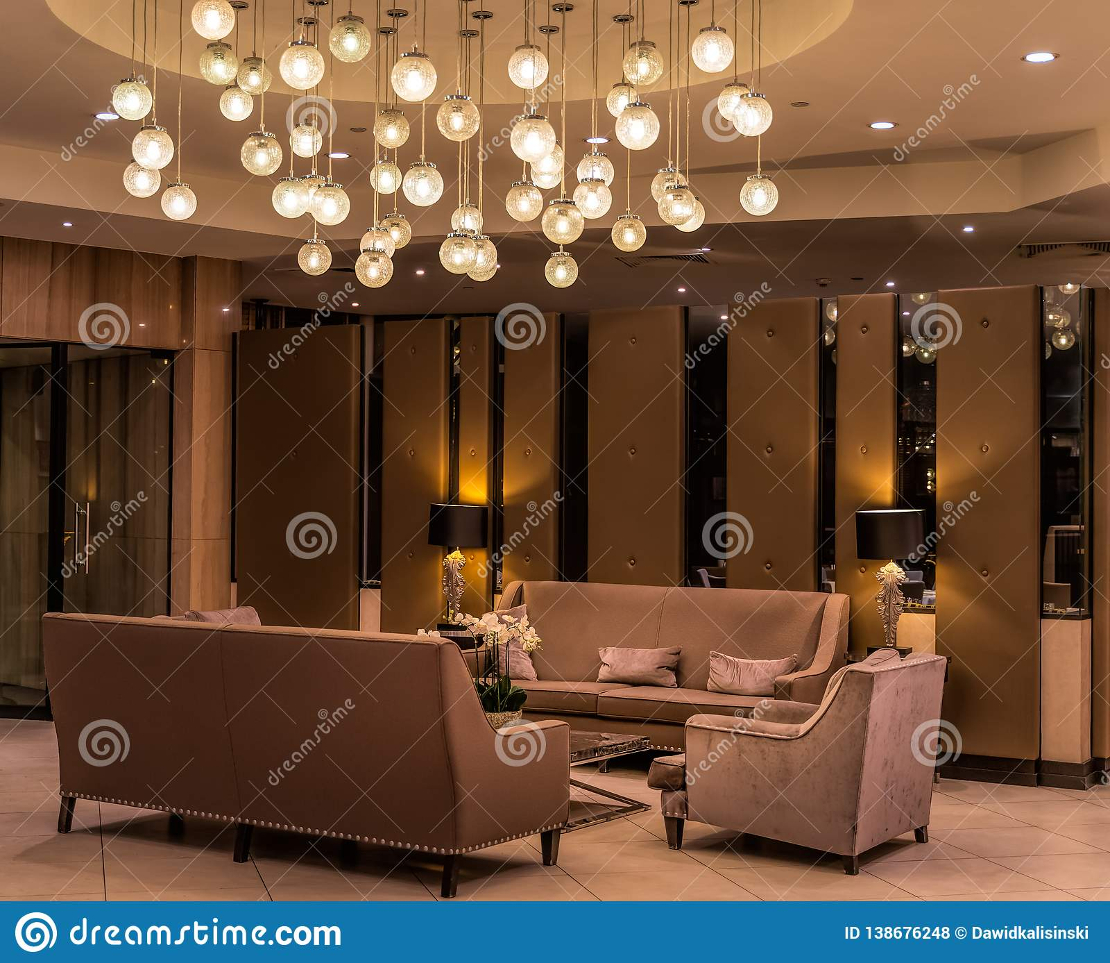 Modern luxurious lobby for hotel with comfortable sofas, arm chairs and moody lighting