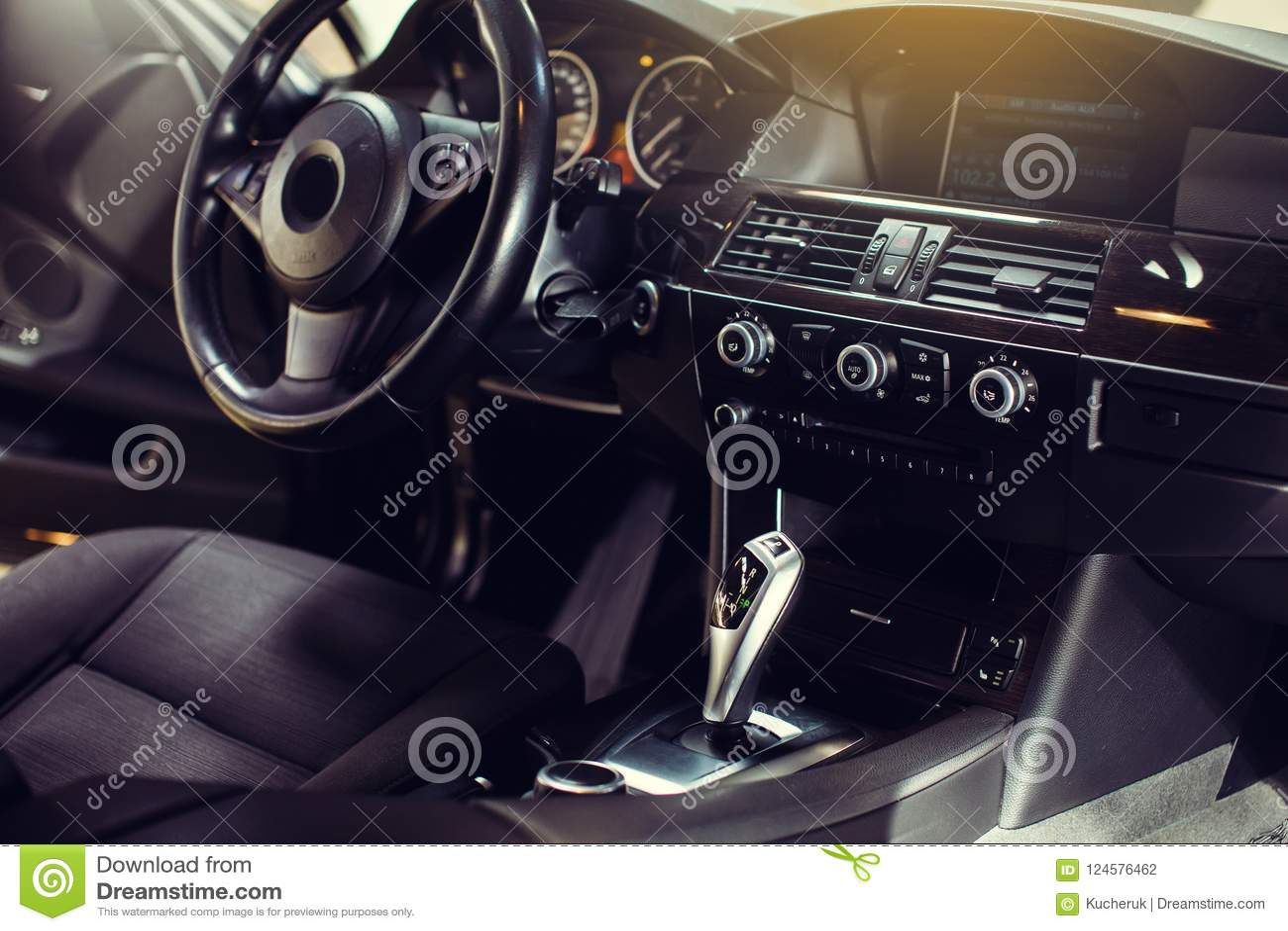Modern luxury car Interior - steering wheel, shift lever and dashboard.
