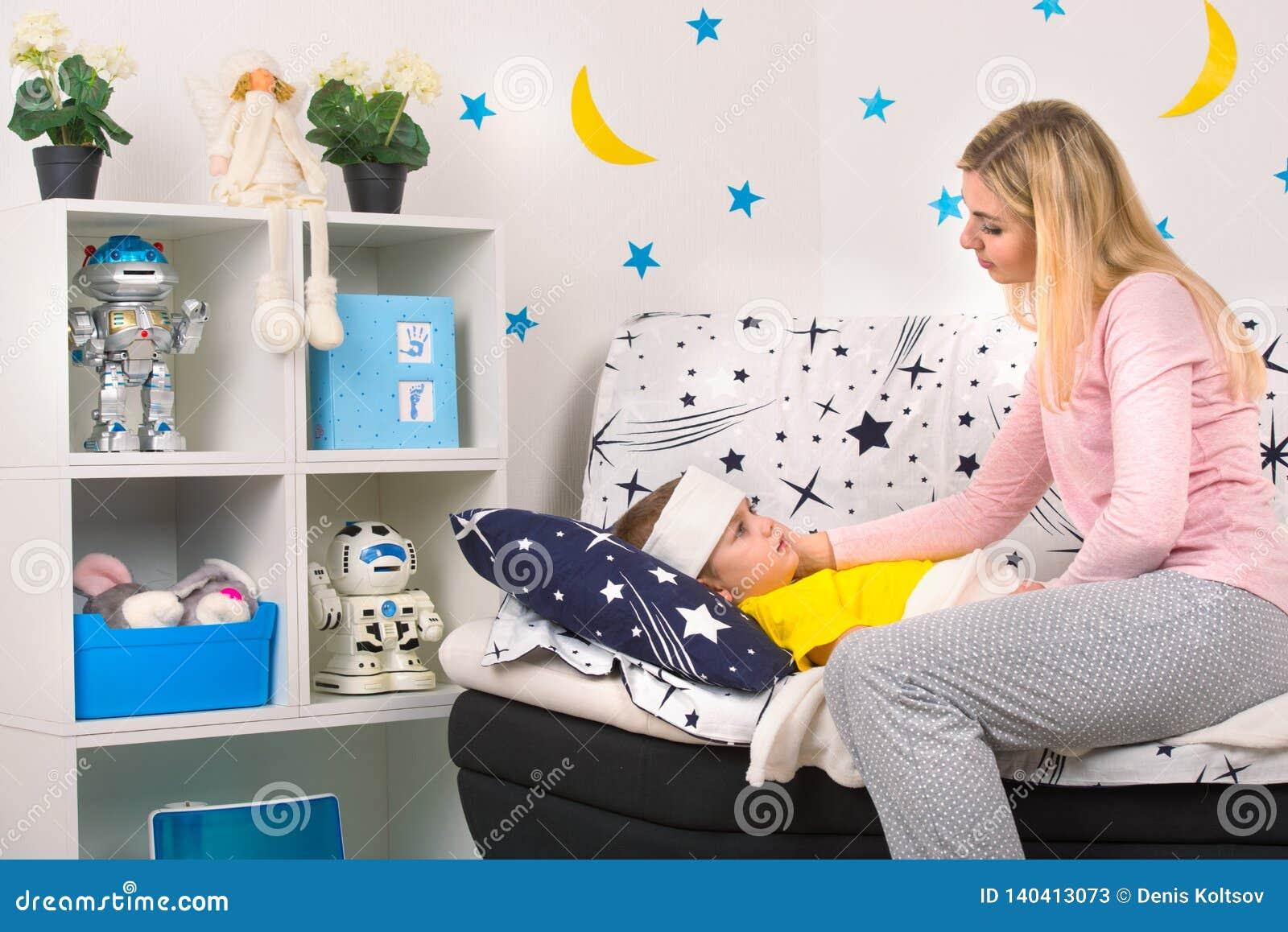 Modern mäter temperaturen med din hand till ditt barn Ett barn med feber som lägger i säng