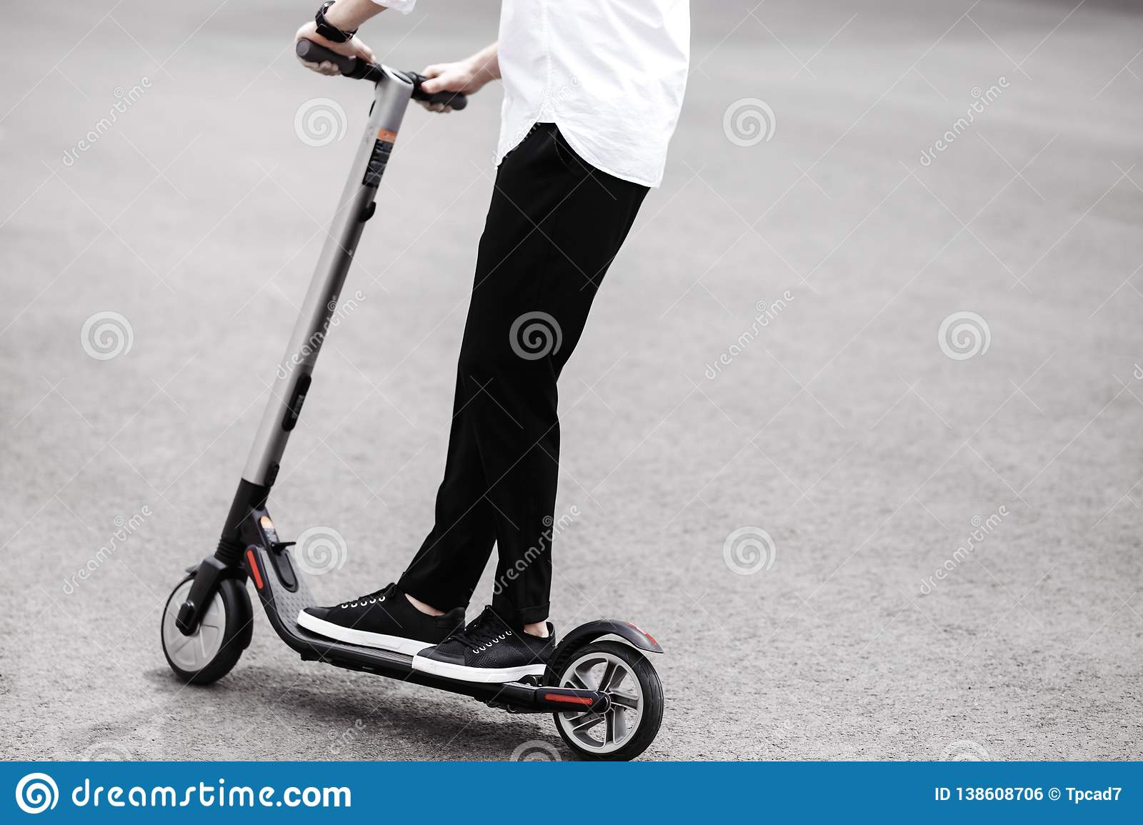 Modern man in stylish black and white outfit riding electric sco