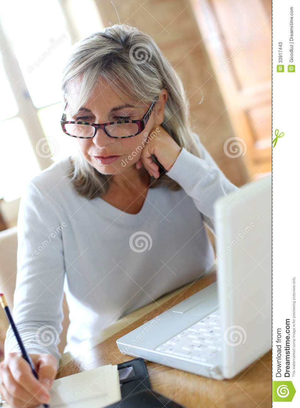 Modern mature woman using laptop at home stock photos for Household bargaining and the design of couples income taxation
