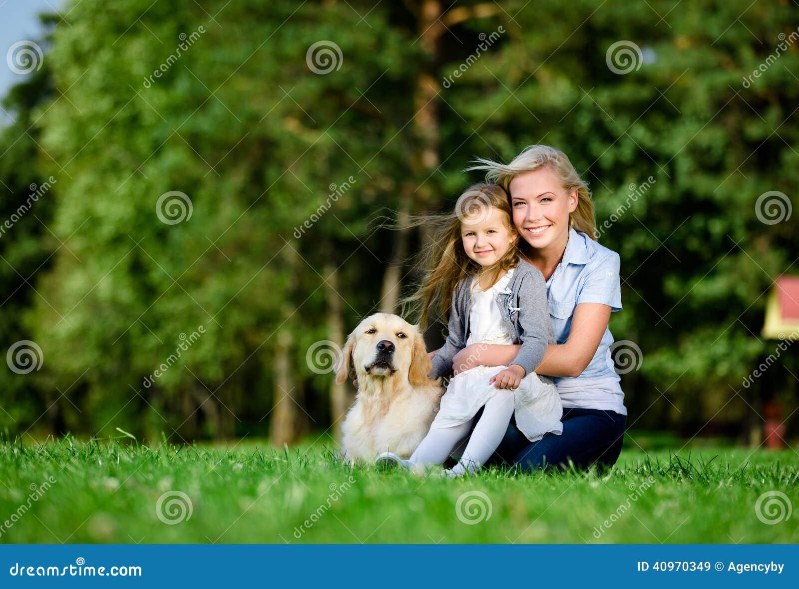 Modern med dottern och labrador är på gräset