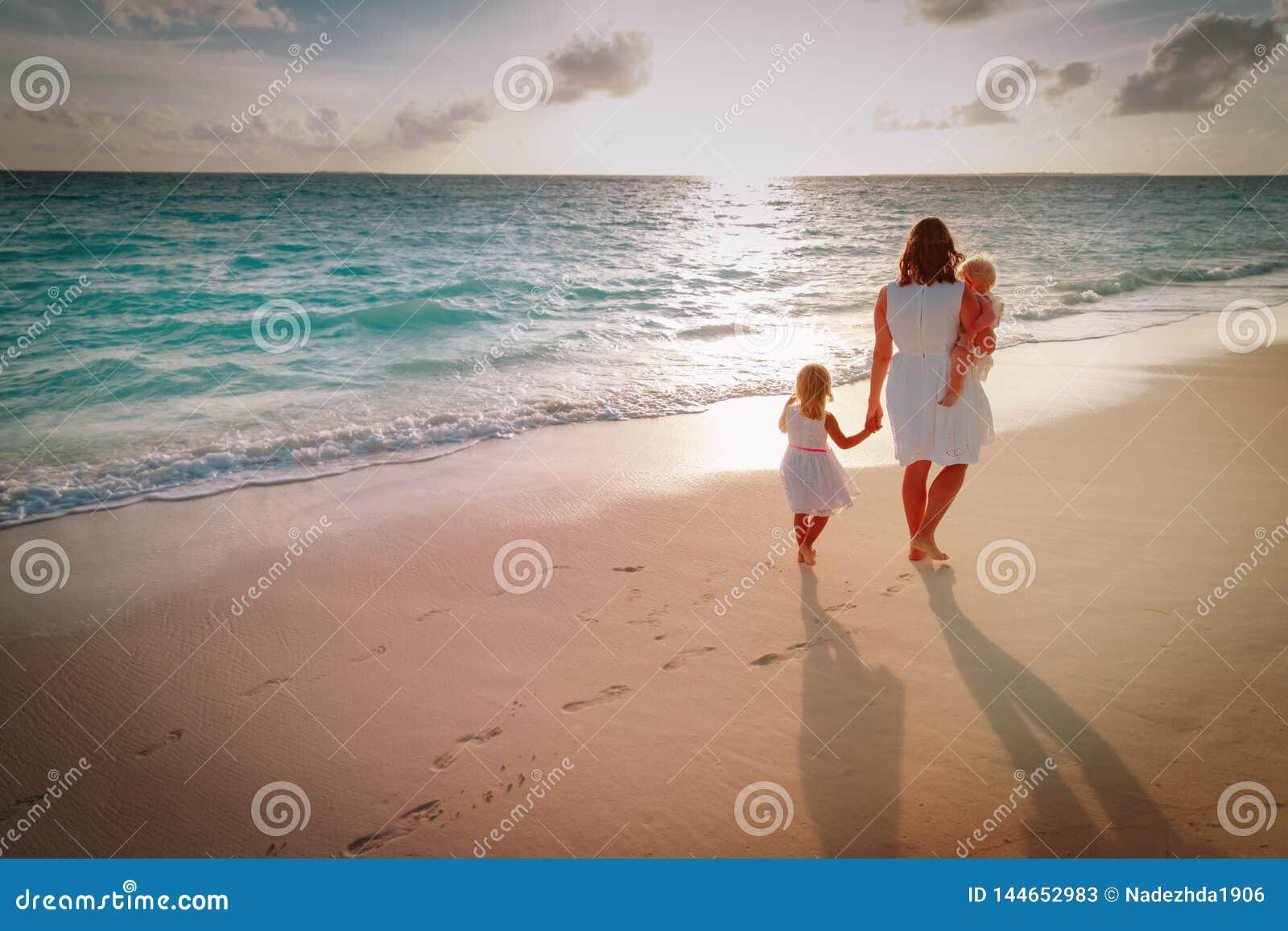 Modern med ungar går på sandstranden