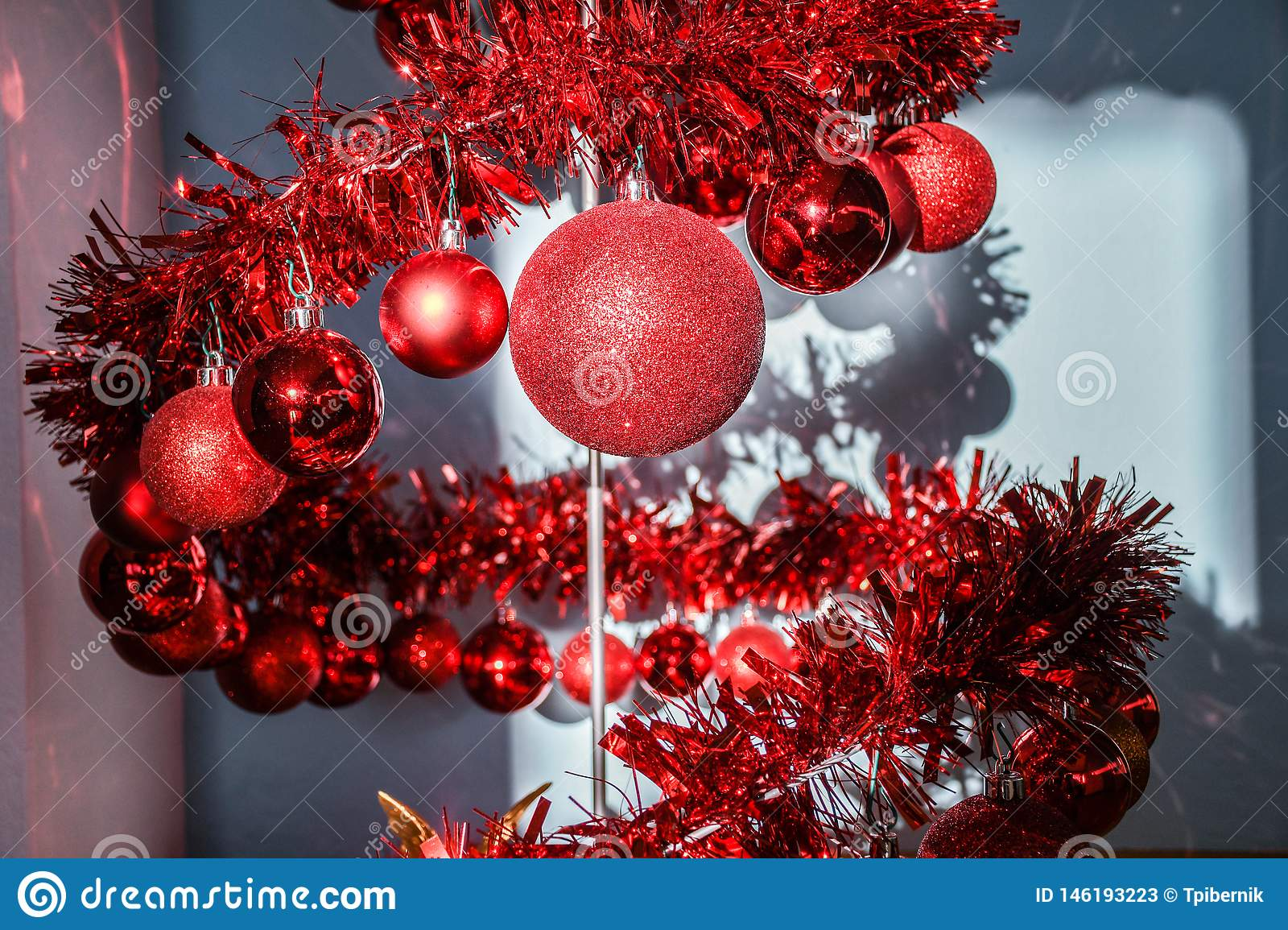 Modern metal spiral Christmas tree decorated with red shiny balls