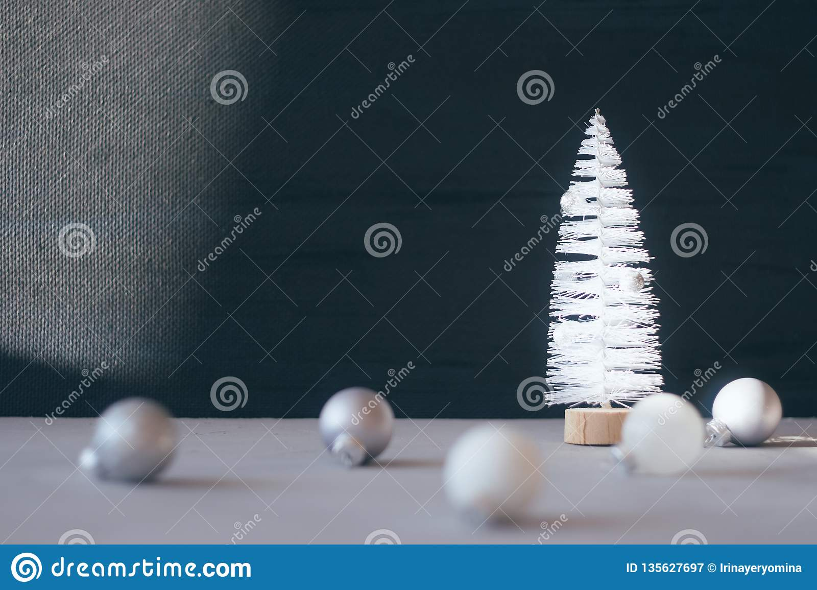 Modern minimal Christmas festive gift winter background. Close up white Christmas tree, silver and white ornament ball on black
