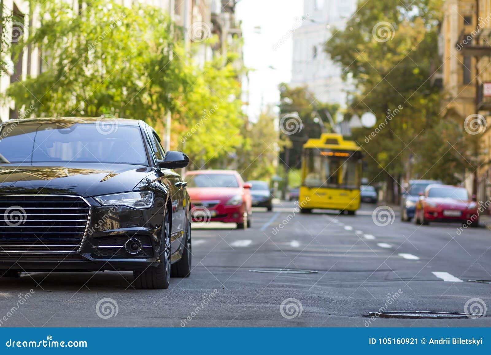 Modern ny bil på sidan av gatan Rader av bilar som parkeras på