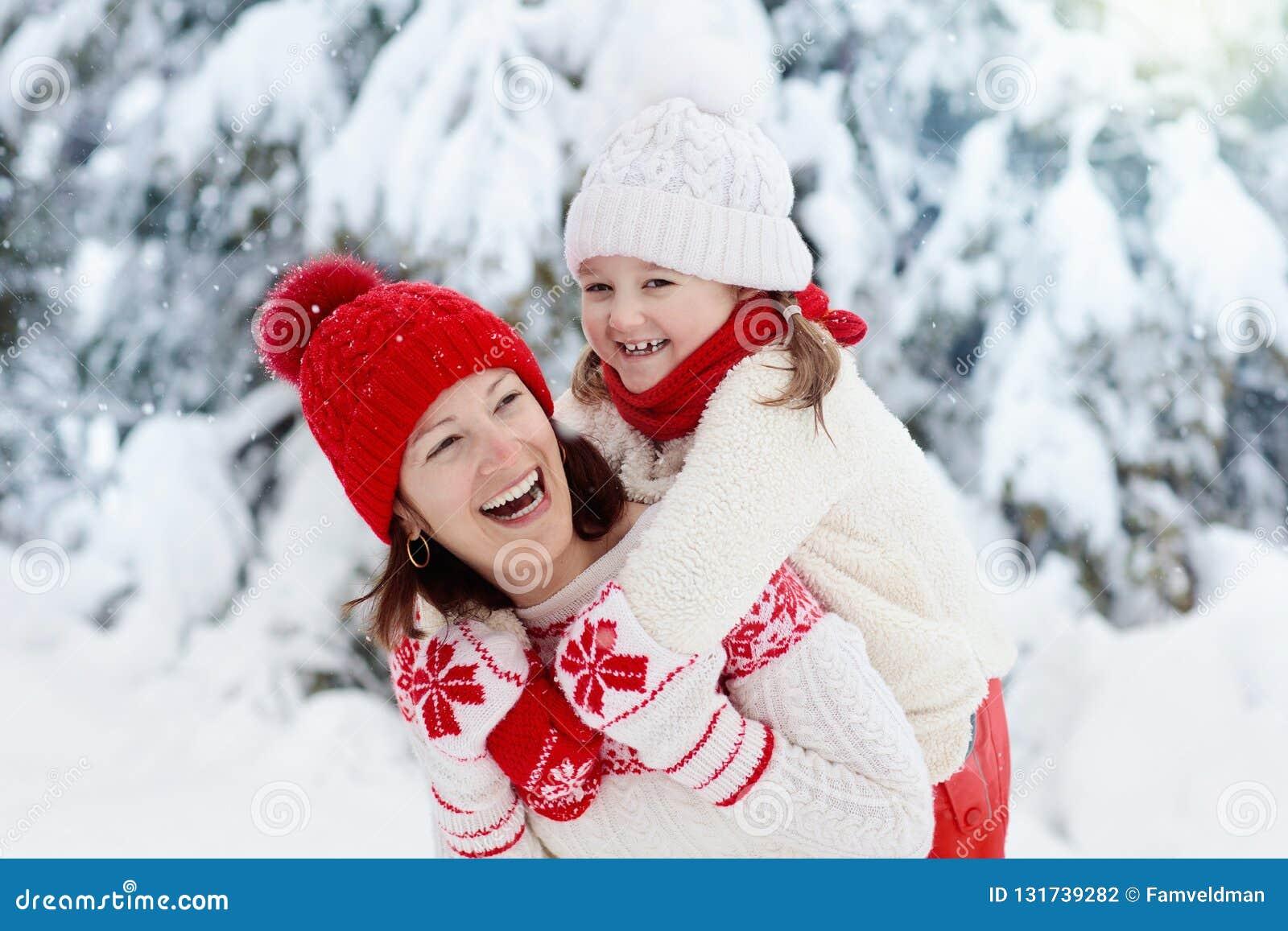 Modern och barnet i stack vinterhattar spelar i snö på familjen som jul semestrar Handgjord ullhatt och halsduk för mamma och ung