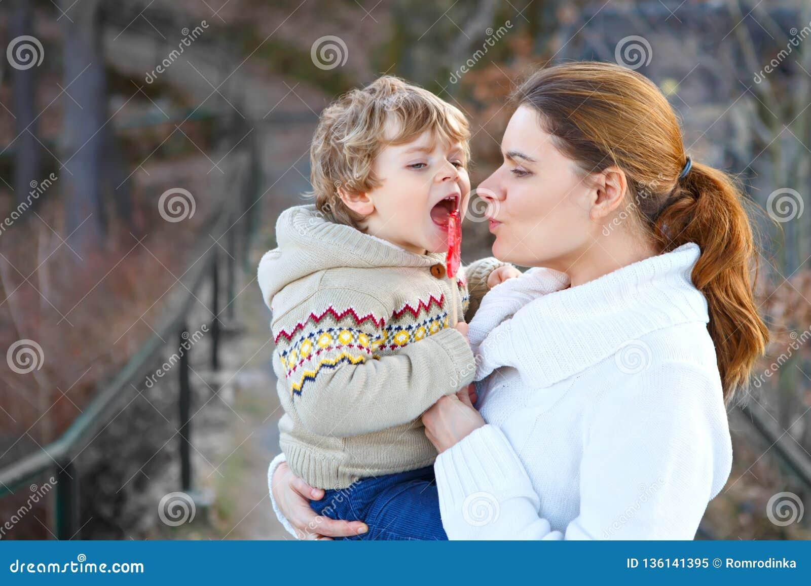 Modern och den lilla sonen parkerar in eller skogen, utomhus Krama och ha gyckel tillsammans Lycklig litet barnpojke och ung mum,