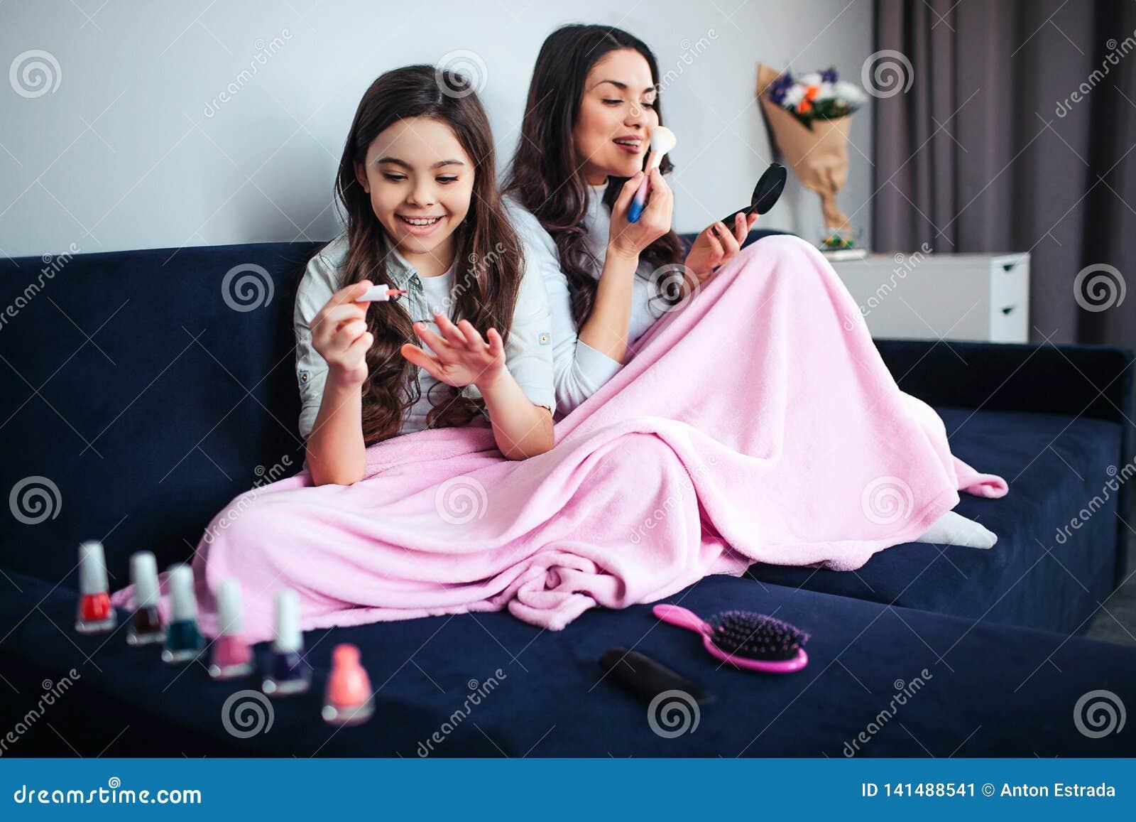 Modern och dottern för härlig brunett sitter den caucasian tillsammans i rum Gilr bruksrosa färger spikar polermedel och leende 1