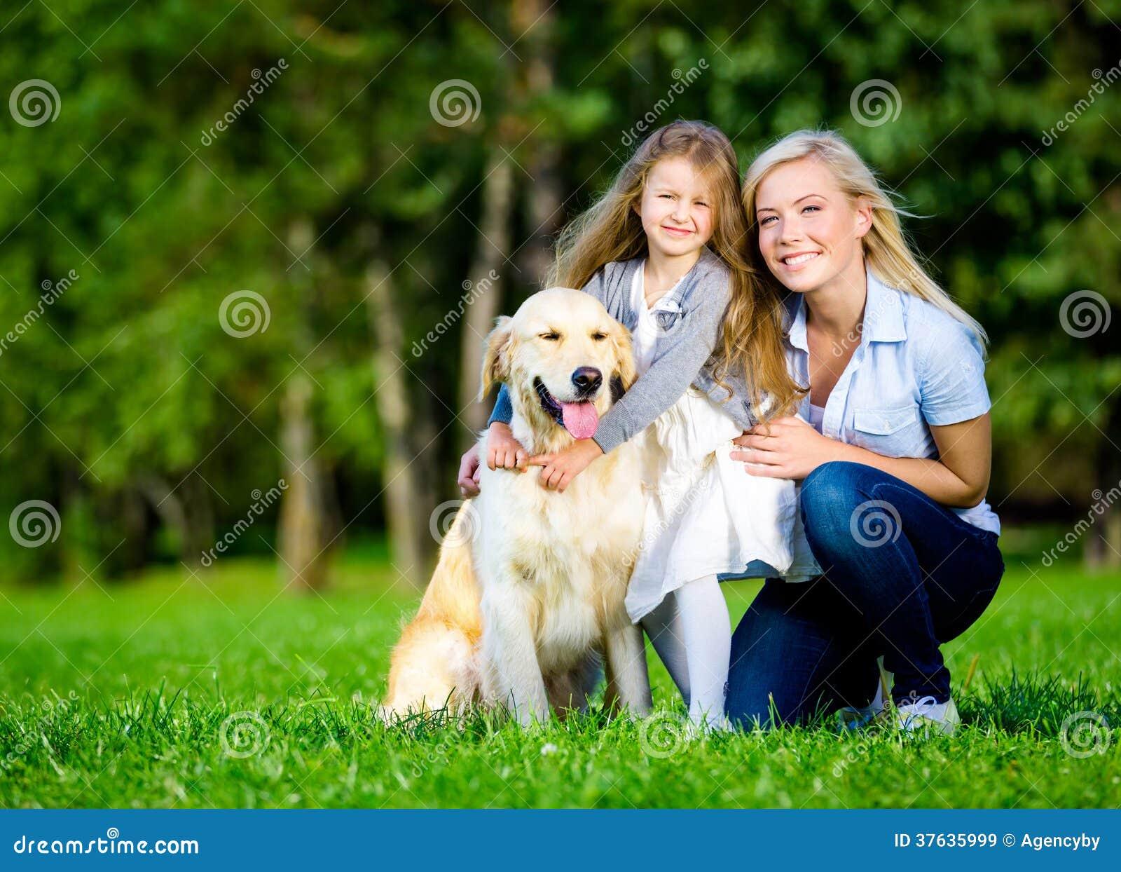 Modern och dottern med labrador är på det gröna gräset