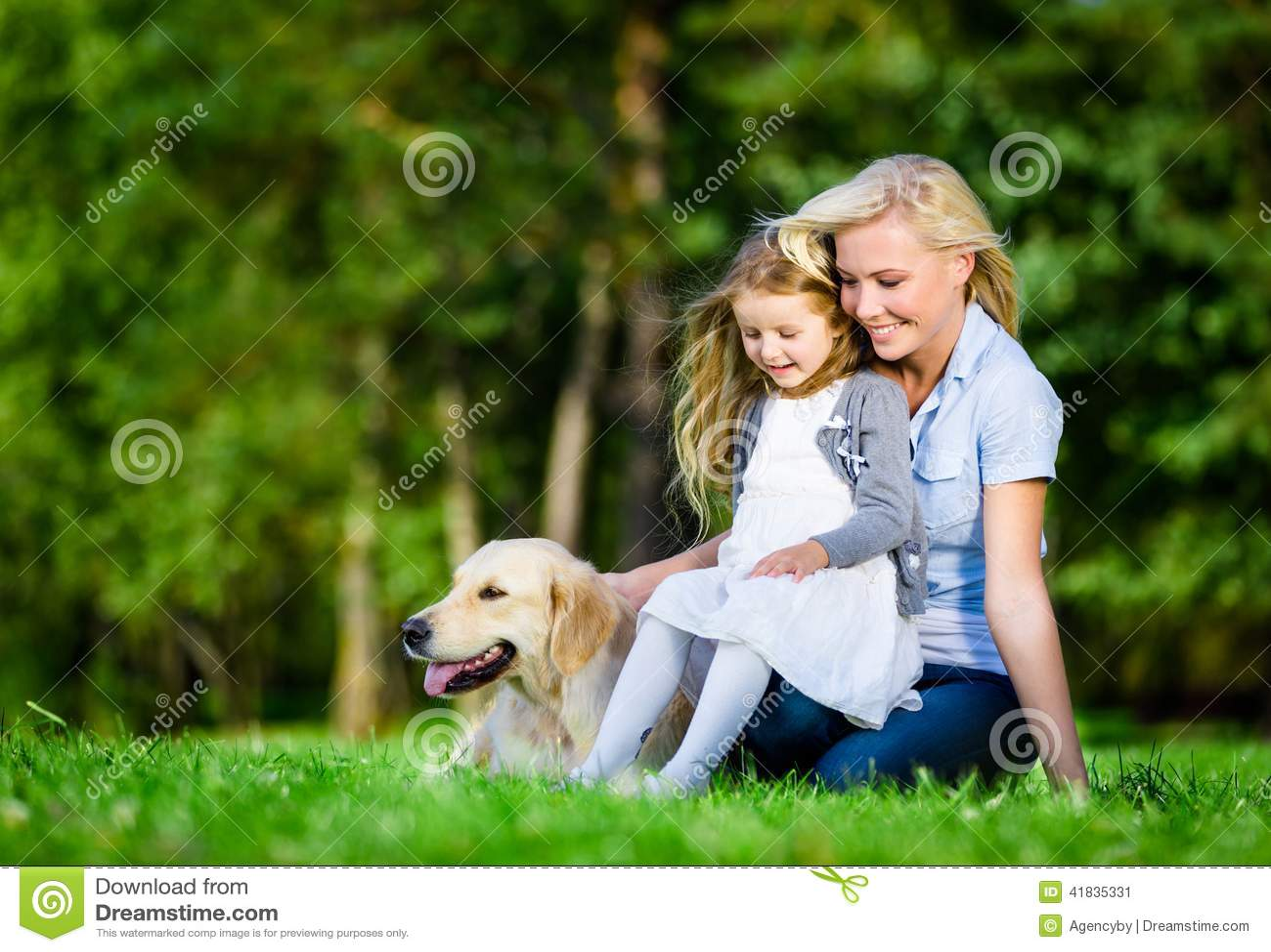 Modern och dottern med labrador är på gräset