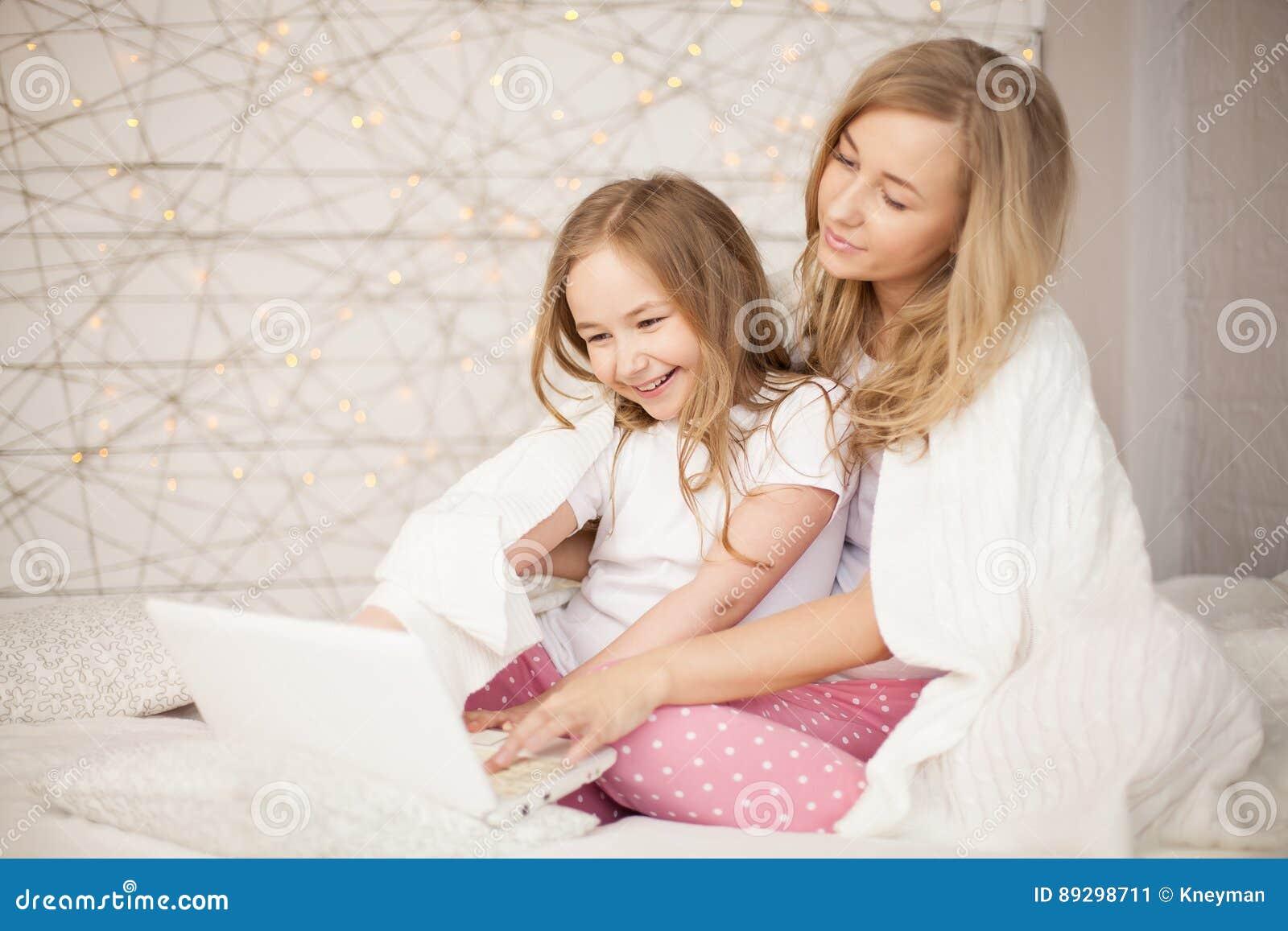 Modern och dottern sitter på säng i pyjamas och har gyckel, använder bärbara datorn livsstil lycklig familj Utbildning lär