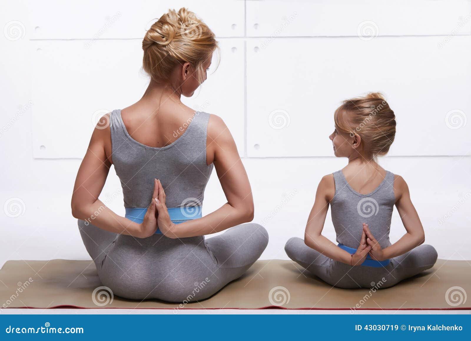 Modern och dottern som gör yoga, övar, kondition, idrottshallen som bär de samma bekväma träningsoverallerna, familjsportar, spor