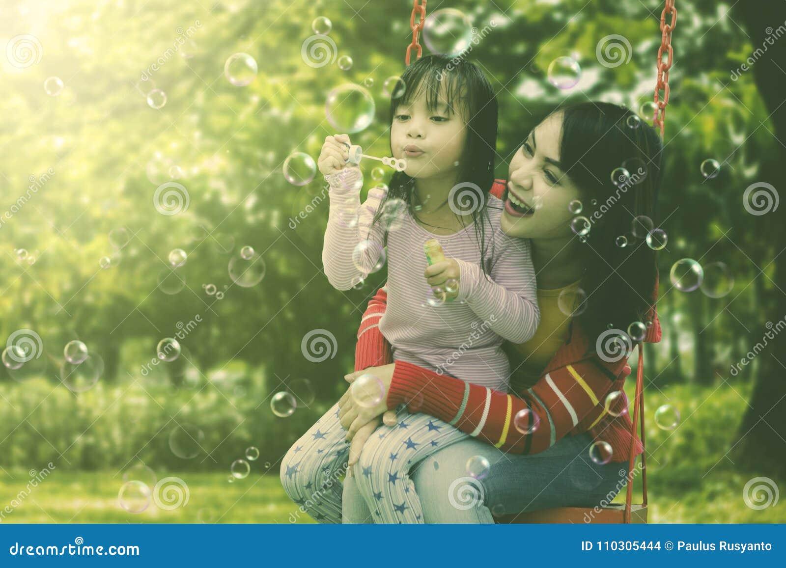 Modern och dottern som har gyckel som blåser såpbubblor på, parkerar