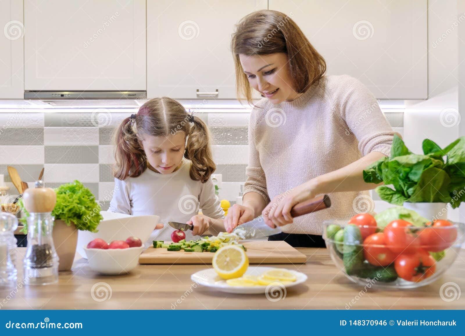Modern och dottern som tillsammans lagar mat i kökgrönsaksallad, förälder och barn, talar att le