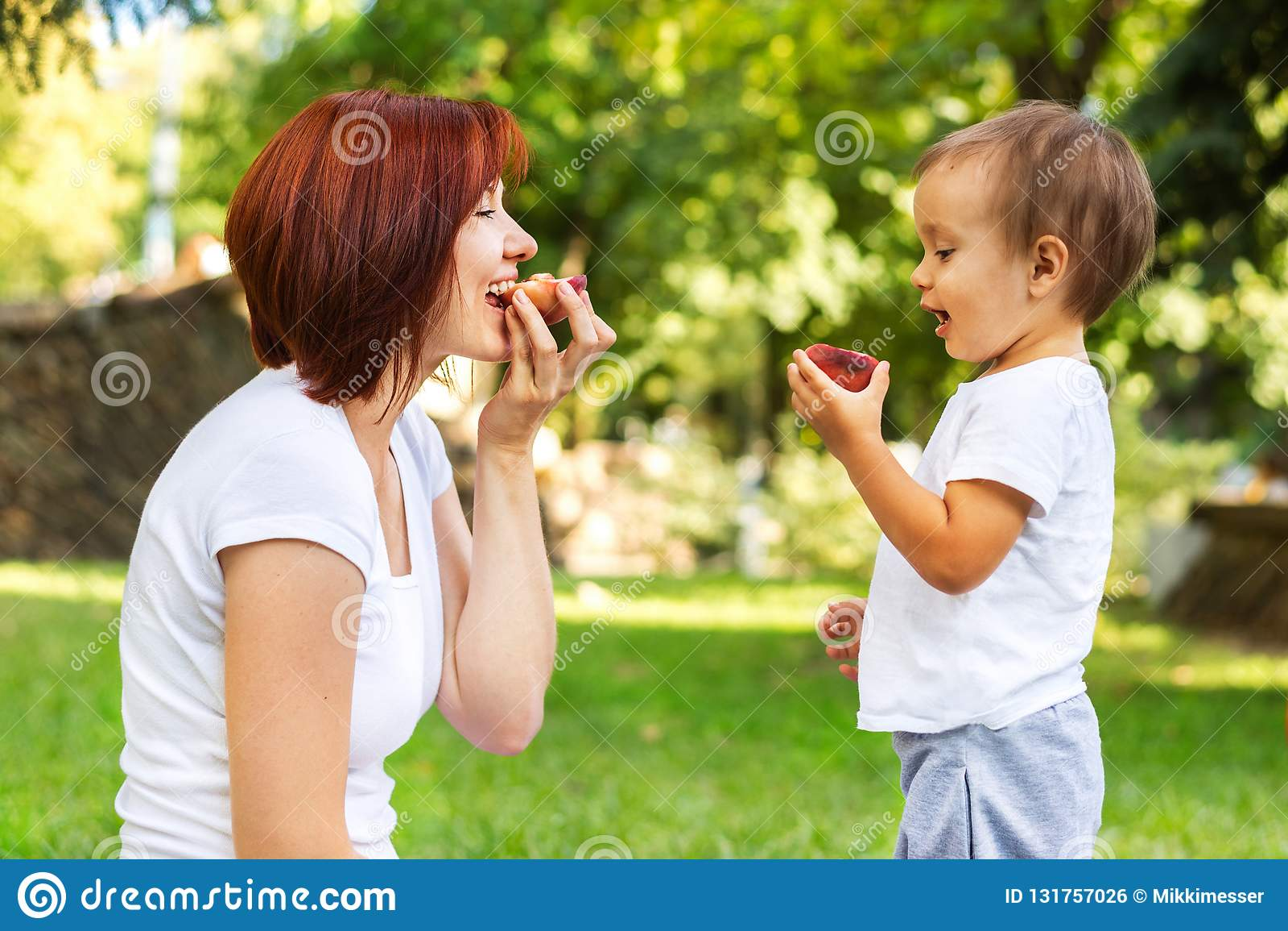 Modern och sonen som äter persikan på en picknick i, parkerar Mamma och son som delar en utomhus- frukt Sunt uppfostra begrepp